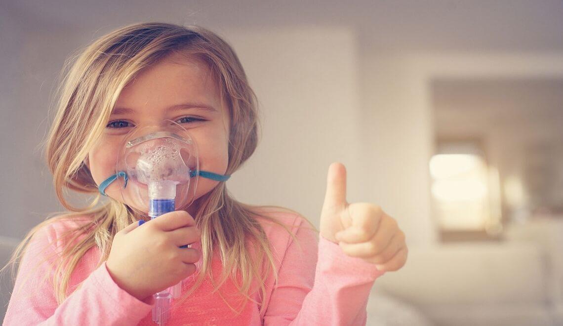 bambina sorridente fa aerosol