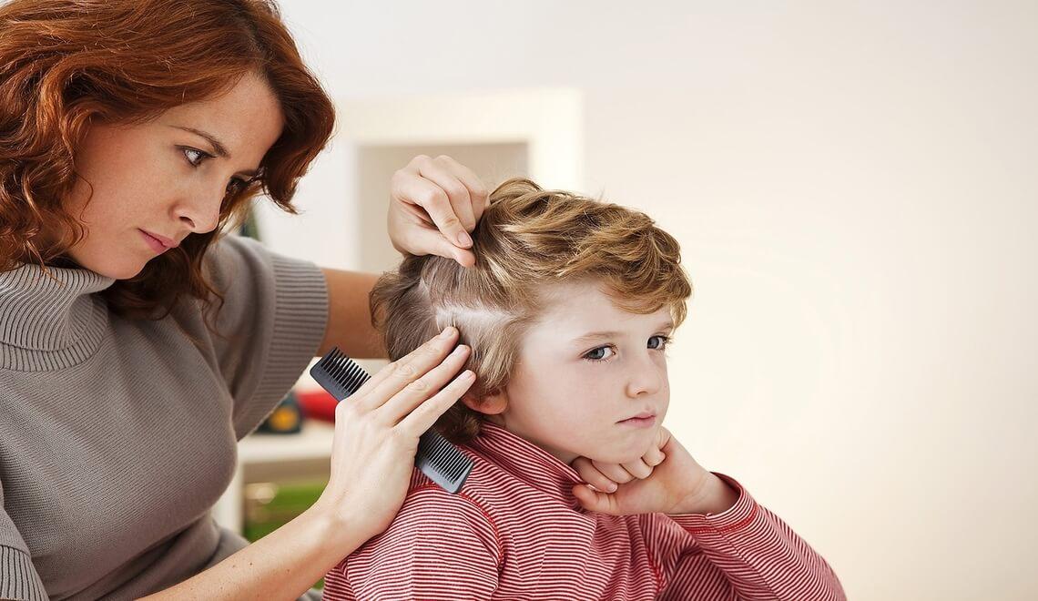 una mamma controlla la testa del bambino per prevenire i pidocchi