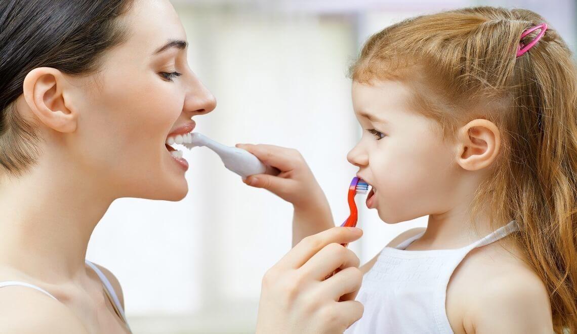 mamma e bimba che praticano igiene dentale