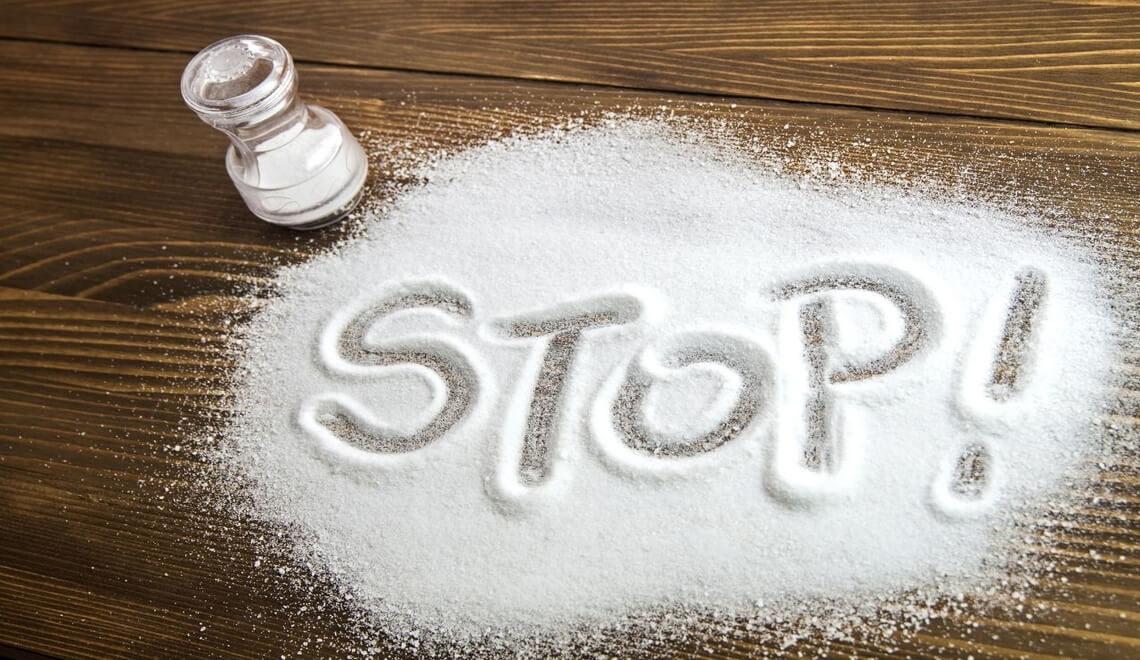sale sulla tavola con scritta stop a indicare dieta povera di sodio